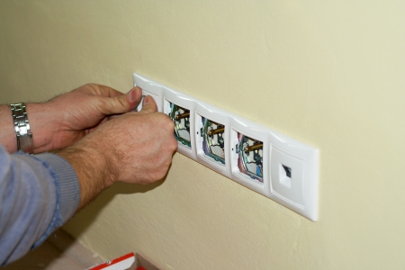 Electrician completes sockets on 230 volts into boxes in the wall. The sockets are in multiple frame together with LAN socket. photo
