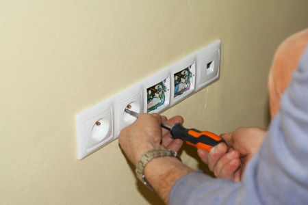 Electrician mounted outlet to 230 volts in a box in the wall with a screwdriver. The sockets are in the frame along with multiple PC connection LAN socket. photo