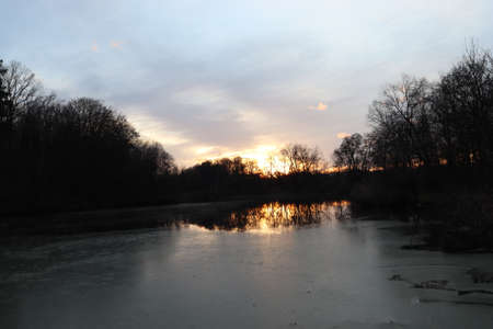 Sunset over a partially frozen pond. Shadows of trees around the pond.