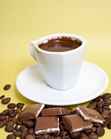 coffee with chocolate squares over a yellow background Stock Photo - 9099459