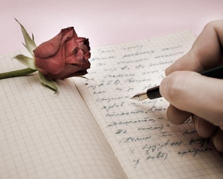 cartas antiguas: escribir una carta de amor con una rosa sobre fondo Rosa Foto de archivo
