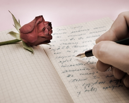 fountain pen writing: write a love letter with a rose over pink background Stock Photo