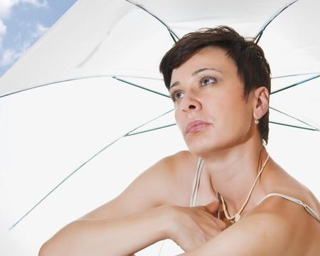 beautiful woman under a beach umbrella photo