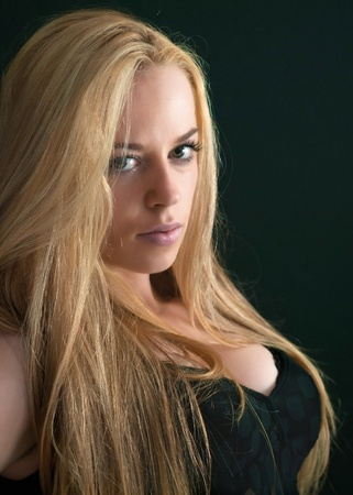 sexy blonde looks at the camera over dark background Stock Photo - 10407143