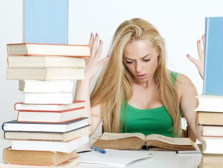 Beautiful blonde being depressed while studying for an examination at her desk Stock Photo