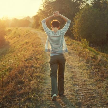 caminando: mujer que camina en la naturaleza final de la tarde, foto color