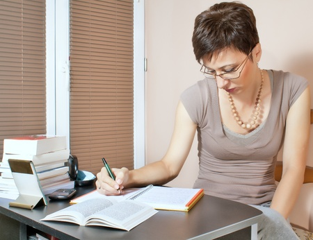 Beautiful woman working at home on agenda photo