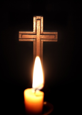 christian candle: cross and candles over dark background