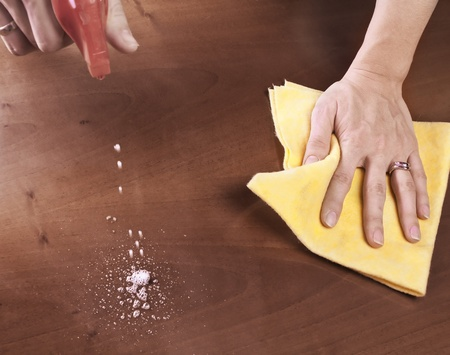 Female hand cleaning dining table photo