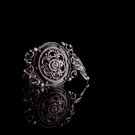 part of a very old bracelet on a black background with reflection photo