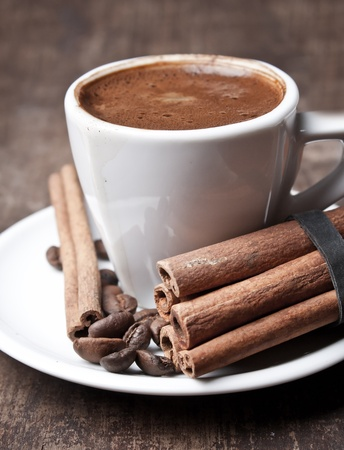 cup of coffee and cinnamon on old plank photo