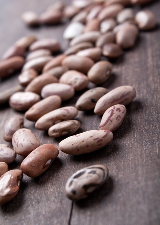 close up photo of different kinds of beans on old plank photo