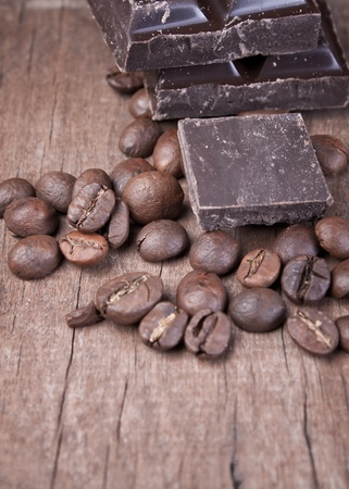 raw coffee beans and chocolate on old wooden plank Stock Photo