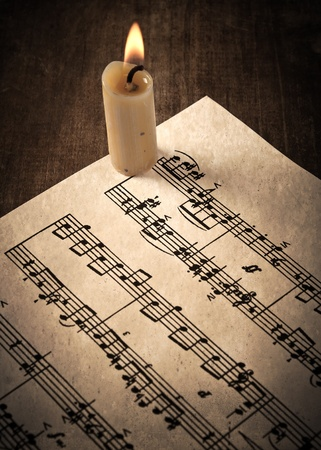 candle illuminates the music paper on wooden table photo