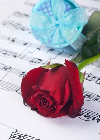 Red rose and gift box  on notesheet photo