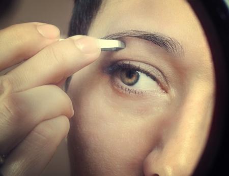 tweezing eyebrow: close up photo of tweezing eyebrows