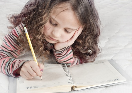 little girl with notebook and pen in bed photo