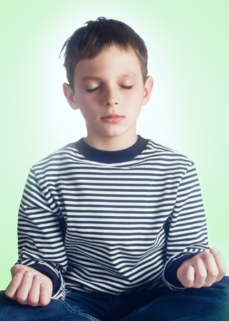 high spirited: The little boy in a lotus pose meditates  Yoga