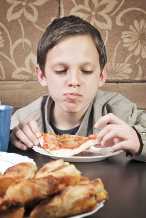 Young Boy Eating Pizza photo