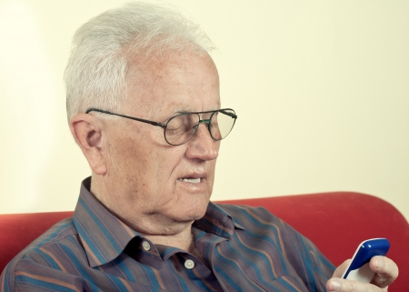 Elderly man looking at a mobile phone photo