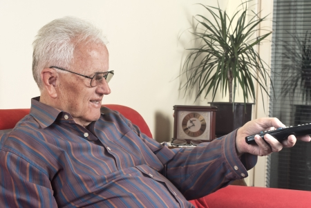 old man on the sofa with television remote control
