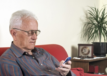 Elderly man looking at a mobile phone Stock Photo - 13624096