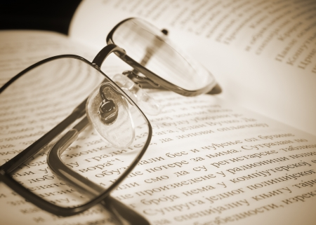 Eyeglasses on the old thick book. A photo close up photo