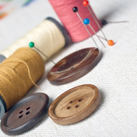 Many bobbin of thread with needle and button on table Stock Photo - 13821445