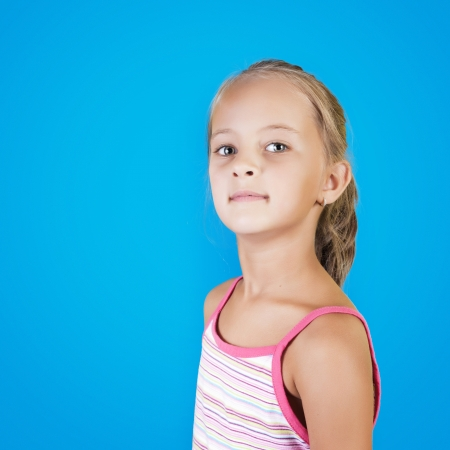 close up portrait of young beautiful little girl in front of a  blue wall photo