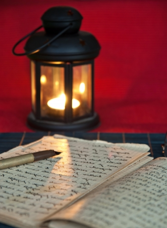 diaries: An open old book by the candlelight,close up photo