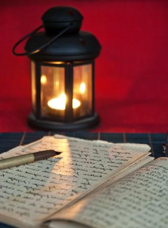 lectura y escritura: Un libro abierto viejo por la luz de las velas, cierre encima de la foto Foto de archivo