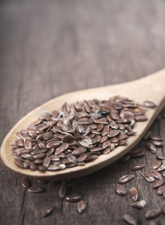 wooden spoon with brown flax seeds on it Stock Photo - 15409561