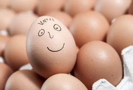 Feche acima da face do smiley em um ovo cru