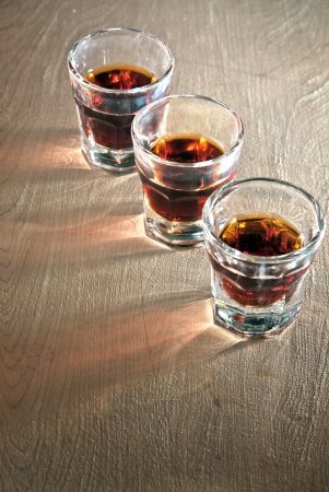 Three shot glasses full of dark colored alcohol on top of a bar table.  photo