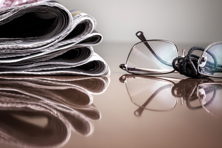 pile of newspaper and glasses on table Stock Photo - 17030830