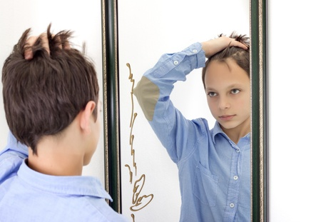horizontal photograph of a young boy combing his hair while looking at himself in a mirror