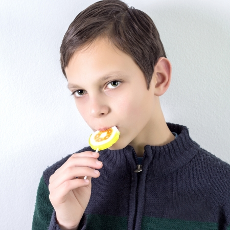 schoolboy with lollipop over white wall,it is not isolated photo