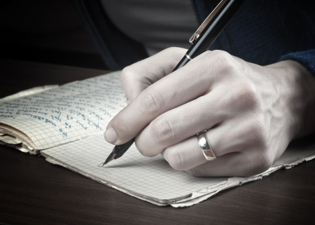 left handed: Left- handed woman writes on a paper,close up photo