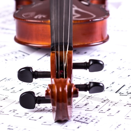 scores: Details of an old violin head on scores
