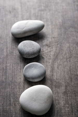 close up of four zen rocks on old wooden plank