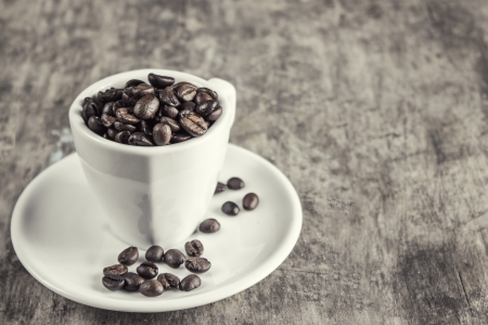 caffiene: Coffee beans in espresso cup,retro style