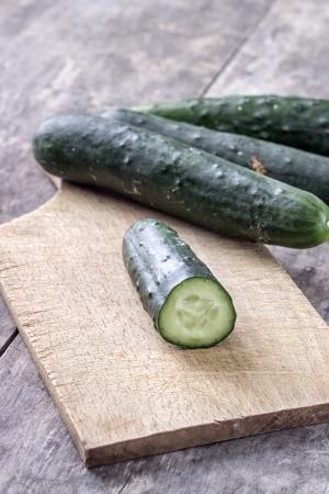 fresh cucumber on cutting board in close up photo