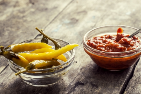 colour intensity: chutney and chillies in glass bowl on table