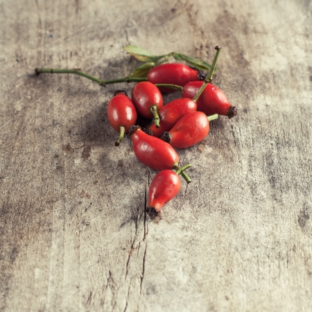 Rose hips on a wooden table, close up photo photo