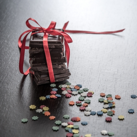 gratifying: Chocolate pieces in decorative ribbon on wooden table