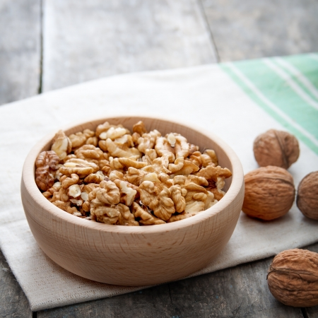 Walnuts in wooden bowl on wooden table