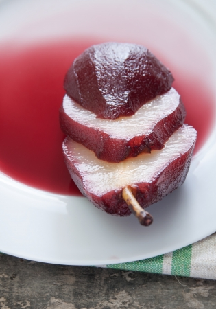 poach: Pear poached in red wine sauce, close up