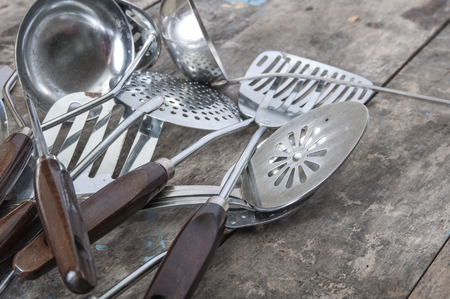slotted: Old Vintage Metal soup ladles and slotted spoon on table Stock Photo