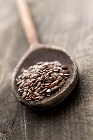 flax seed: wooden spoon with flax seed placed on a wooden table