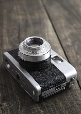 Retro camera over rustic wooden background photo